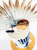 Blue birthday celebration cake with dried flowers and gold sun palm and a chocolate drip on the Isle of Man