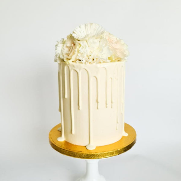 Ivory cream birthday celebration drip cake with fresh flowers on the Isle of Man