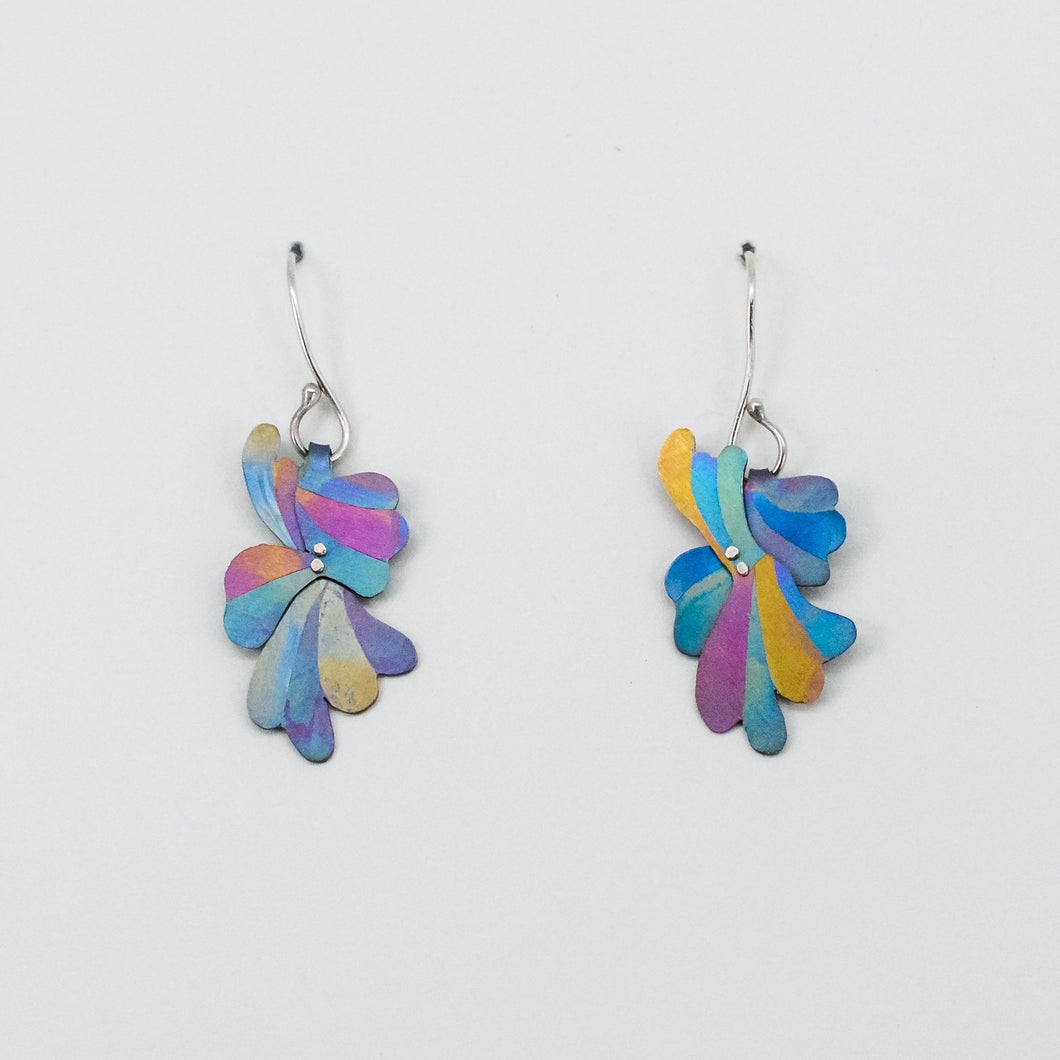 The Flutter of a Full Heart earrings in rainbow, hand-painted with stripes of turquoise, yellow, pink, and blue