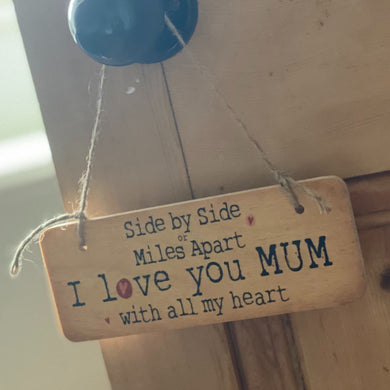 wooden sign saying 'side by side or miles apart I love you mum with all my heart'