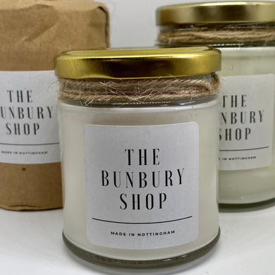 Vanilla and coconut hand poured candle in a glass jar with a white label saying Made in Nottingham