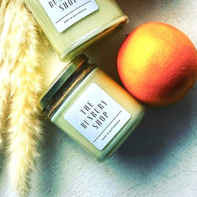 sweet orange and honeysuckle candle next to a fresh orange