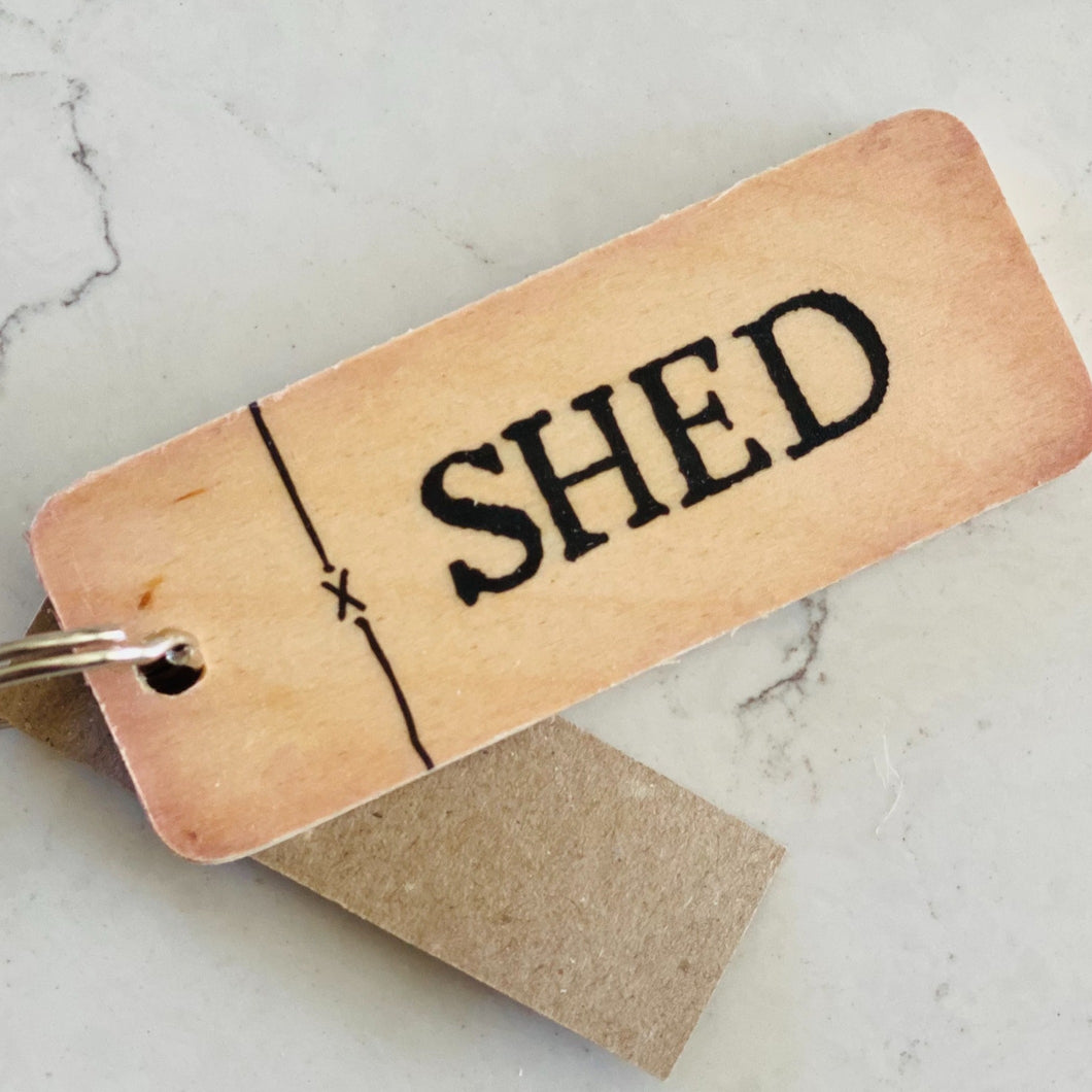 Rustic wooden keyring saying 'Shed'