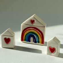 Load image into Gallery viewer, Set of three off white ceramic  houses. The middle features a handpainted rainbow with a red heart above it. The two smaller ones either side feature a small heart in the centre only.