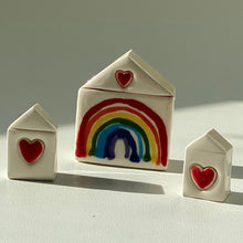Load image into Gallery viewer, Three small rainbow houses. The middle larger has a hand painted rainbow with red heart above and the two smaller ones either side just feature a heart. This set of three can be purchased separately as a set. Only the middle rainbow house is for sale unless specified