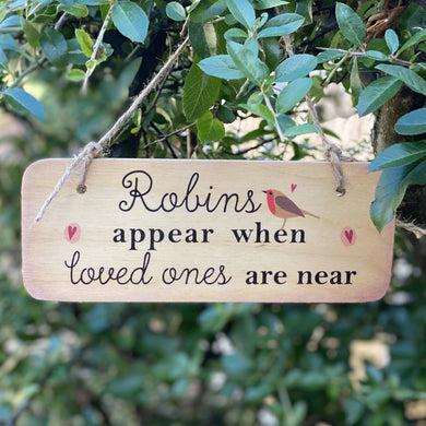wooden sign with wording 'Robins appear when loved ones are near'