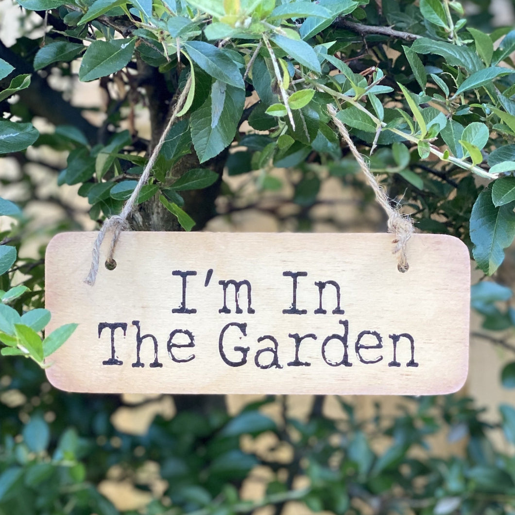 wooden sign with wording 'I'm in the Garden'