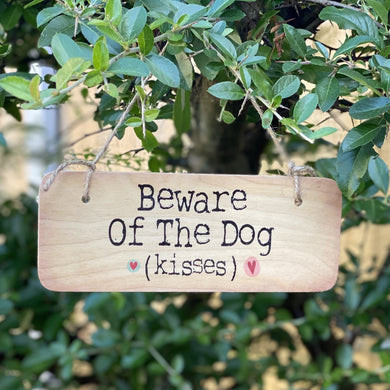 wooden sign with wording 'Beware of the Dog (kisses)