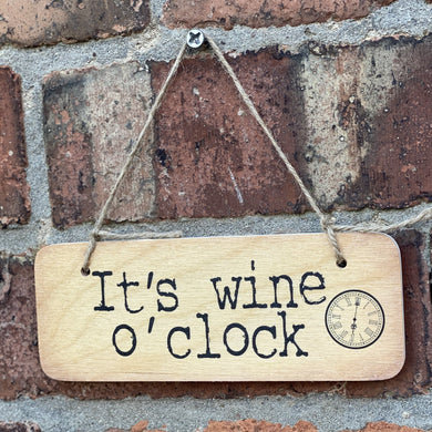 wooden sign with wording 'It's Wine O Clock'