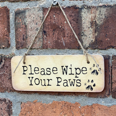 wooden sign with wording 'Please Wipe Your Paws'