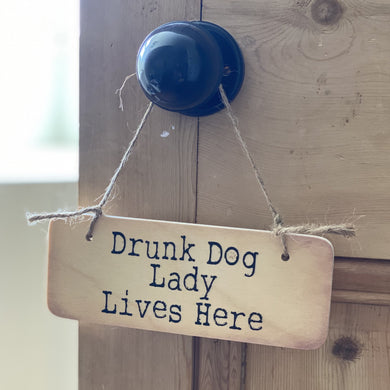 wooden sign with wording 'Drunk Dog Lady Lives Here'