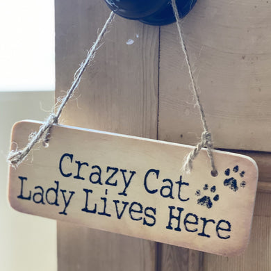 wooden sign with wording 'Crazy Cat Lady Lives here)'