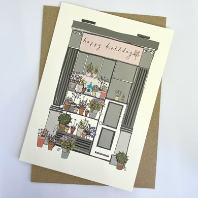 Photo of 'happy birthday' card depicting a hand drawn shop front with various plants in  bloom