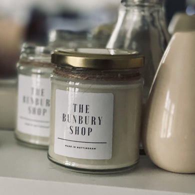 A white, pine scented handmade in Nottingham soy candle on a shelf