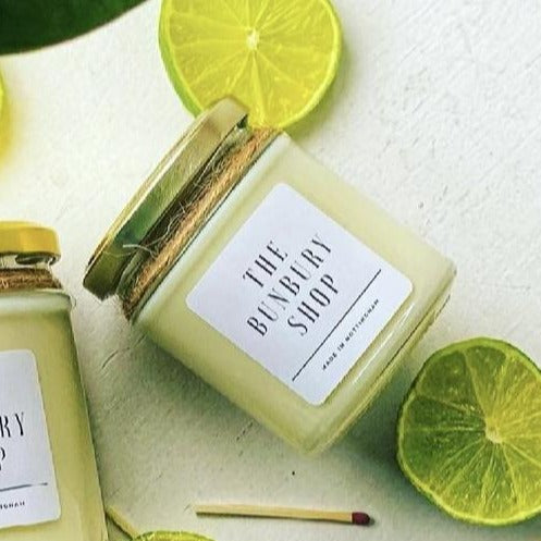 coconut and lime candle with fresh lime and a match stick