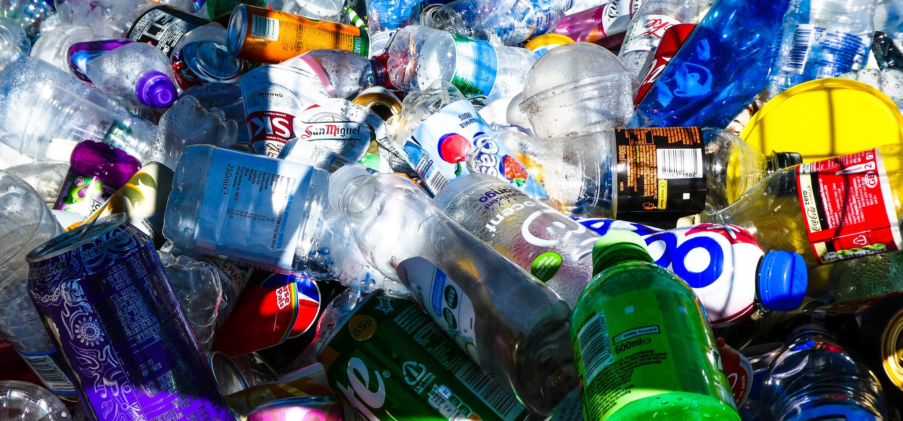 A pile of generally recyclable plastic bottles and cans.