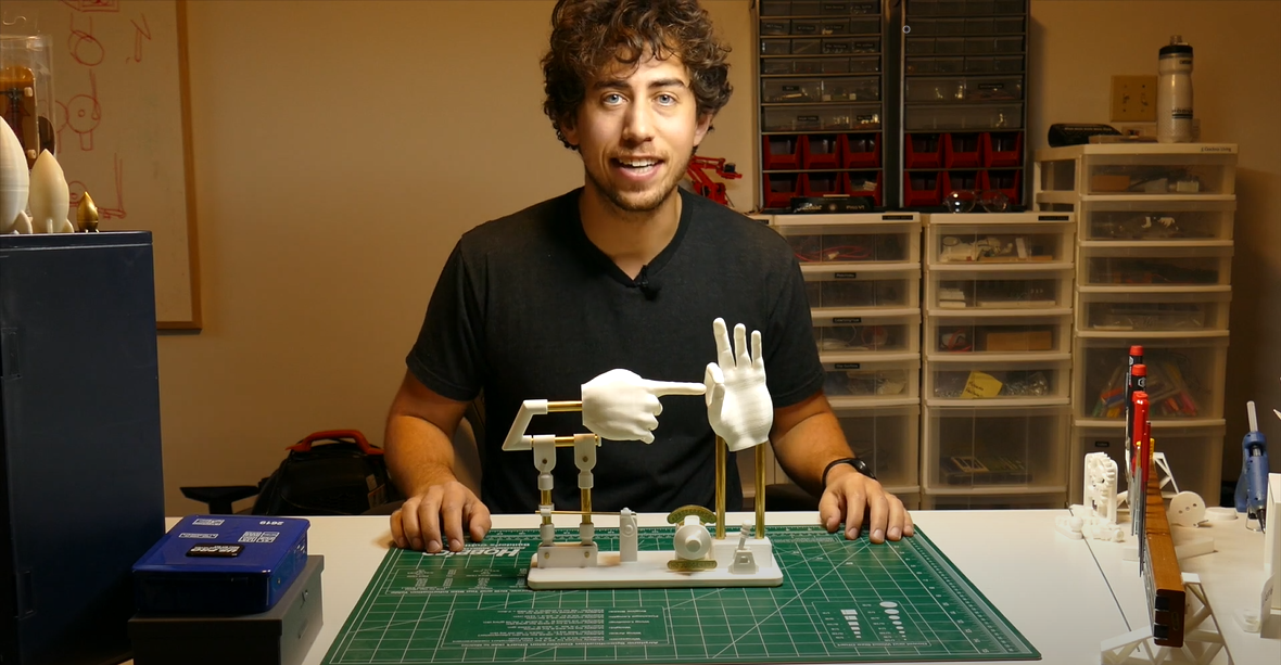 Pic of JBV with his mechanical sculpture depicting a natural act through metaphorical hands