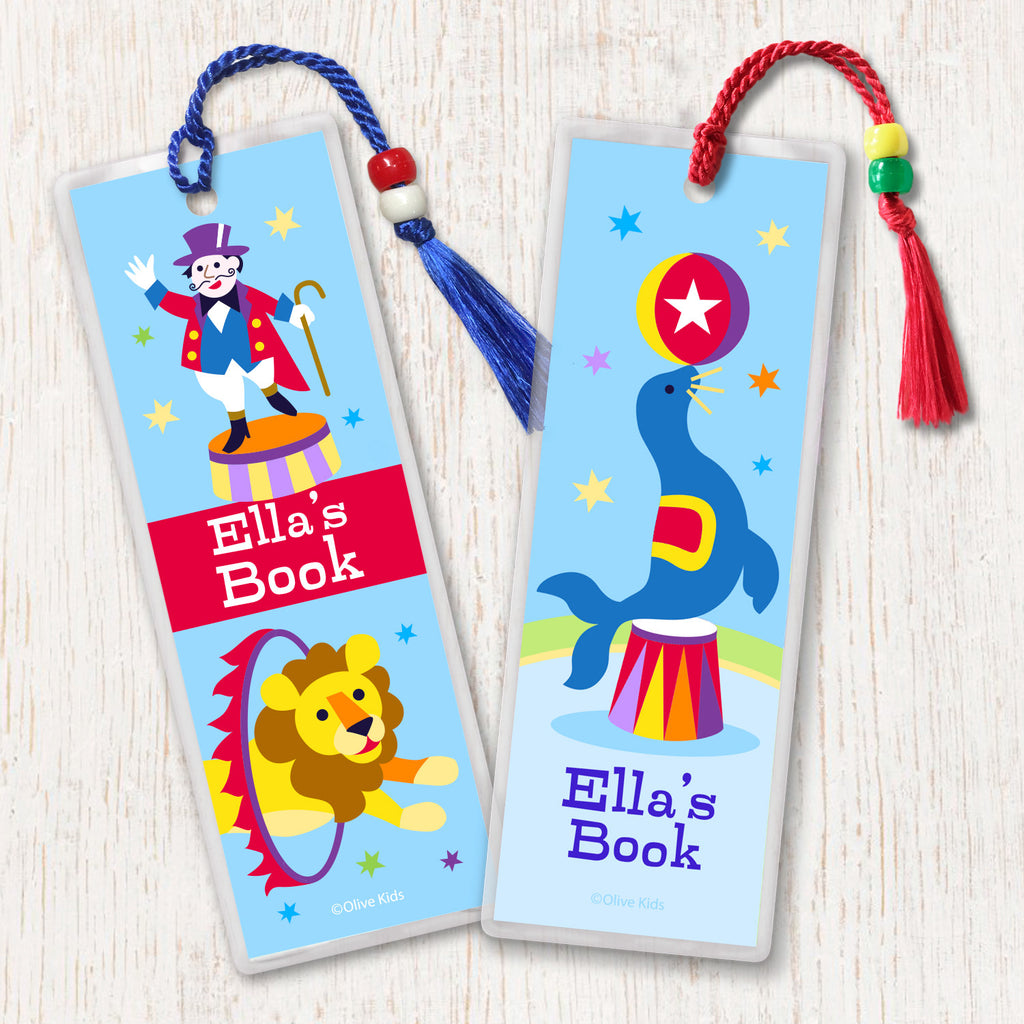 Circus theme kids personalized name bookmarks, one with seal balancing ball and one with ringmaster, both on light blue background.