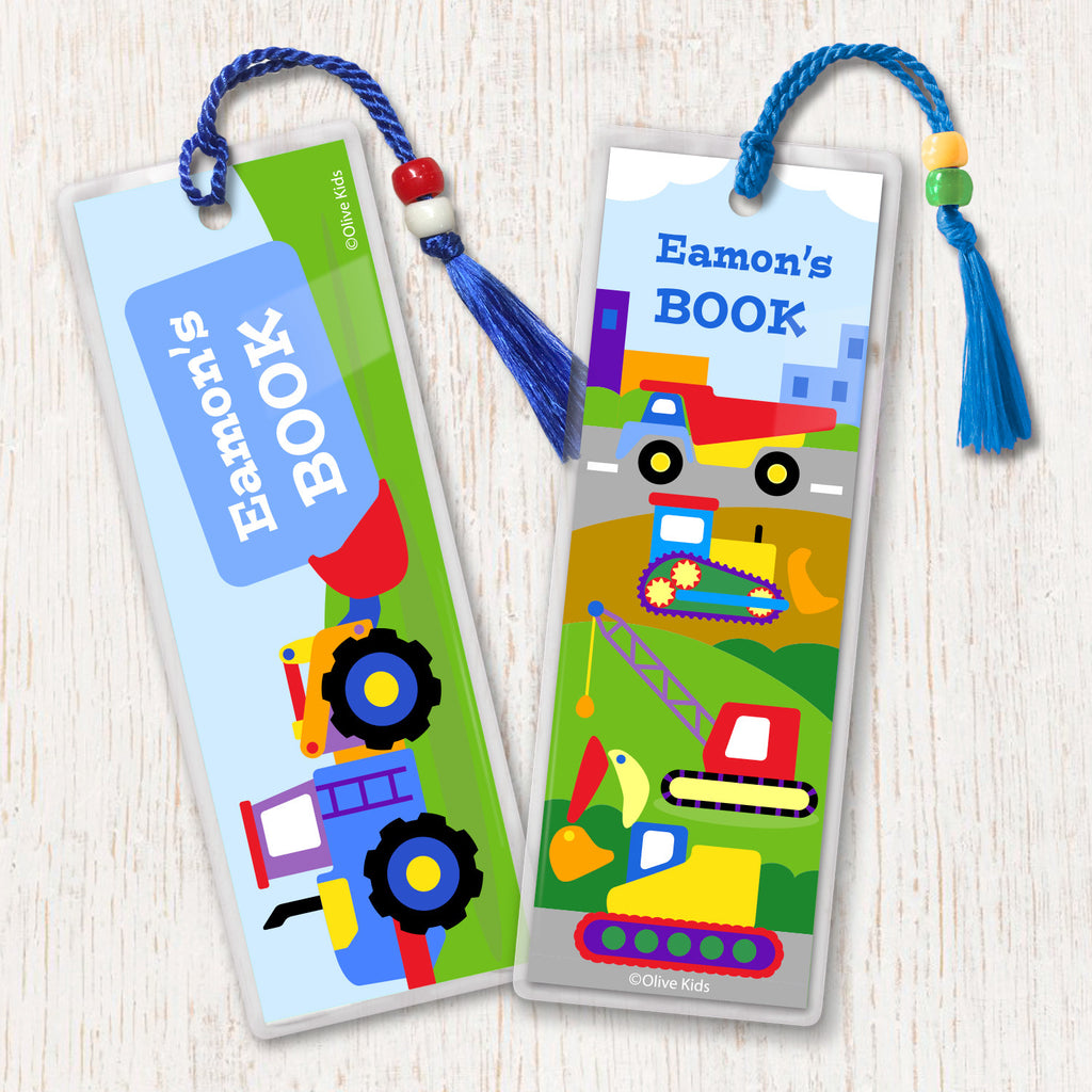 Construction themed kids personalized name bookmarks. Brightly colored trucks on a construction site background, decorated with tassesl and beads.