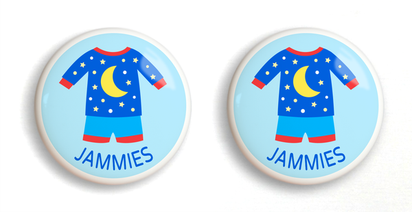 2 ceramic drawer knobs with blue boys pajamas on a light blue ground with the word jammies written below