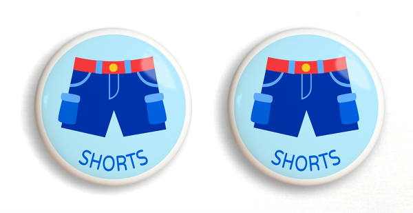 2 Ceramic drawer knobs with boys shorts on a light blue ground with the word Shorts written below