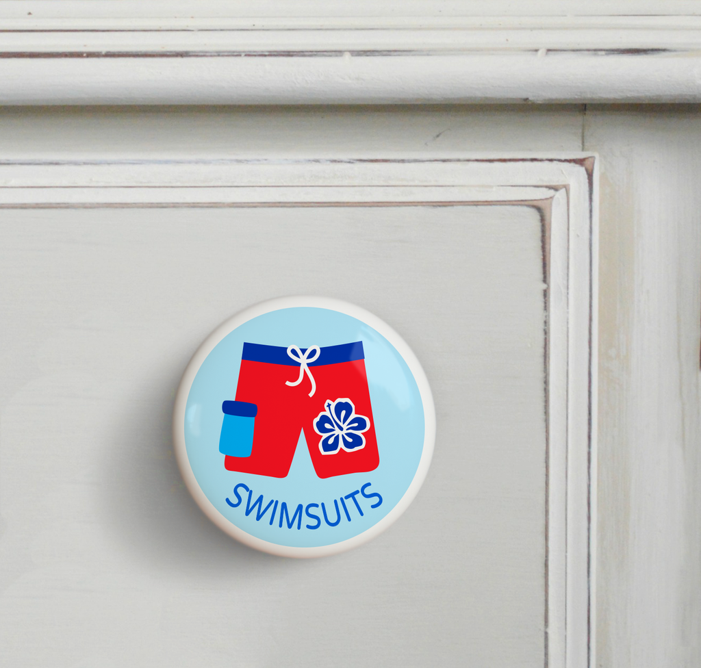 Ceramic drawer knob on a dresser, with boys red bathing suit on a light blue background with the word swimsuits written below