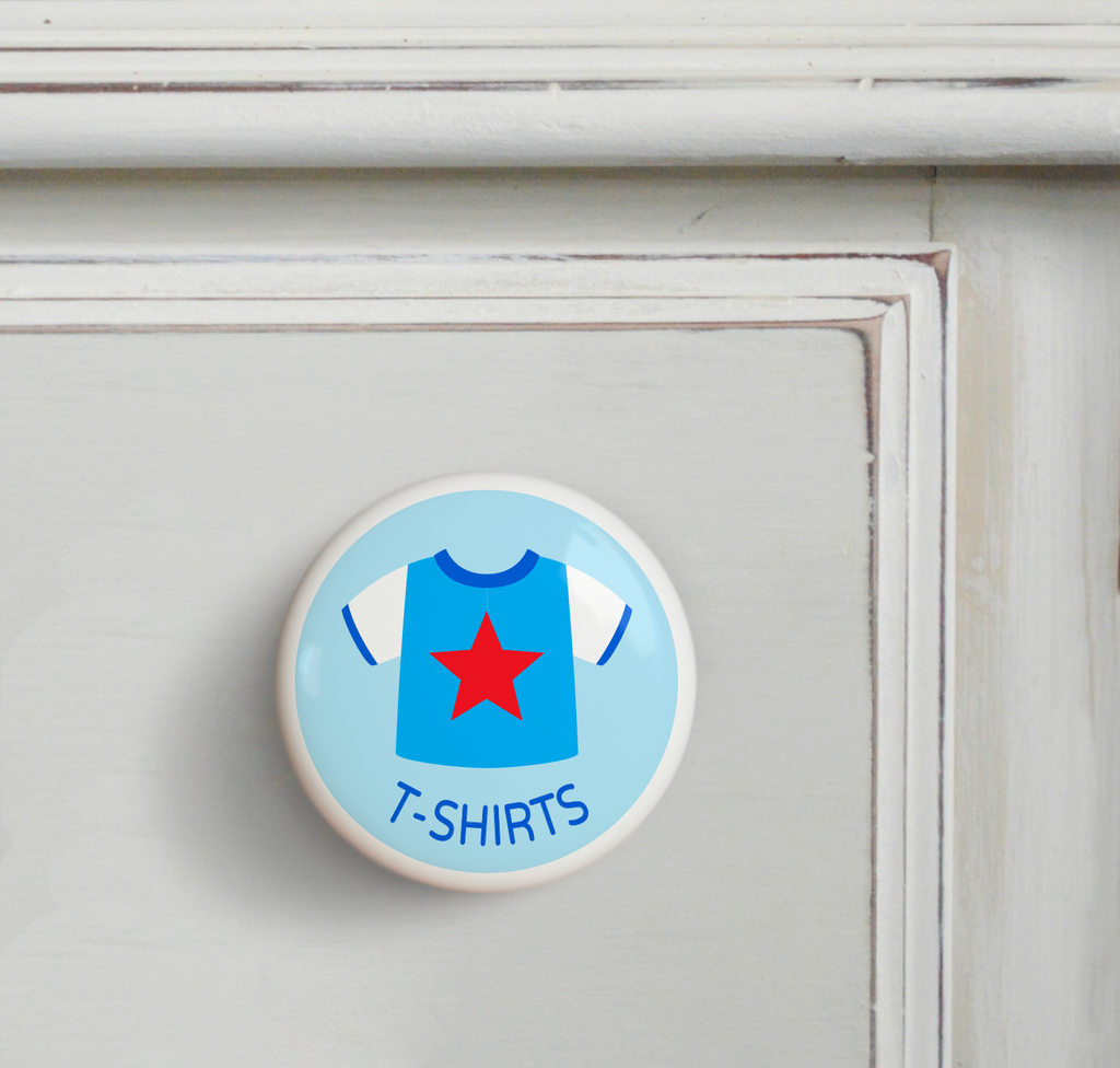 Ceramic drawer knob on a dresser, with boy's t-shirt  on a light blue ground with the word T-Shirts written below