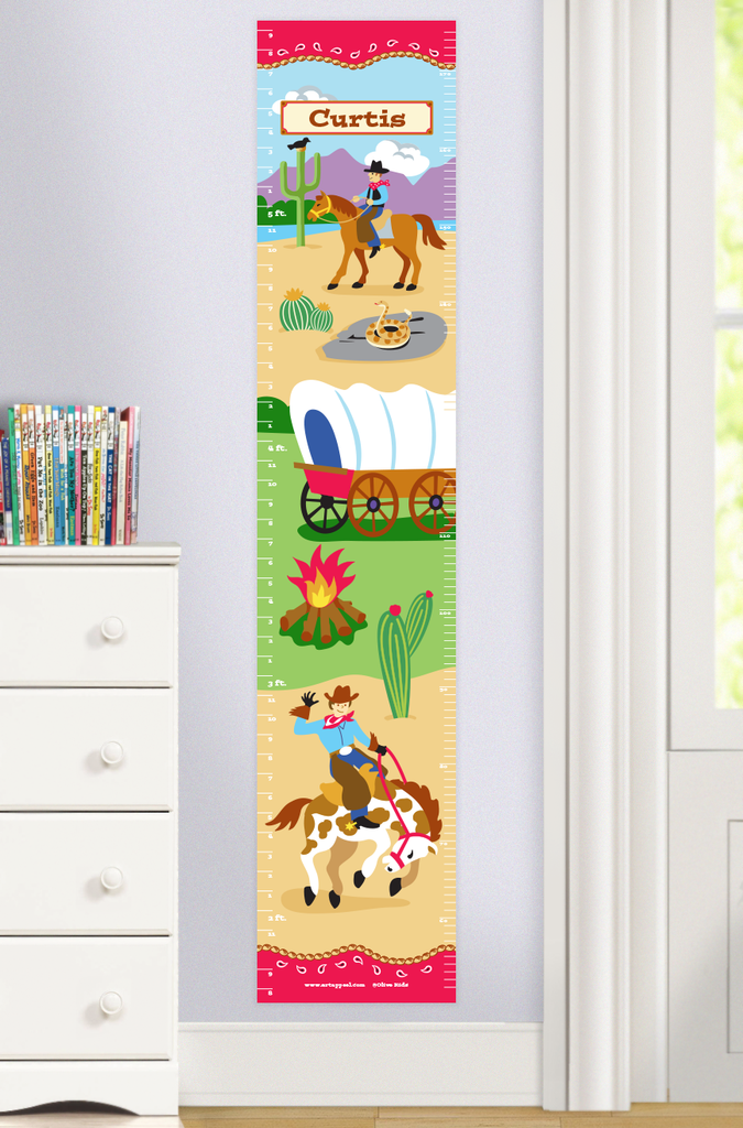 Personalized Cowboy Growth Chart with western scene of cowboys on horses, covered wagon, campfire and cactus. Personalized with child's name at top. Photographed in room scene.