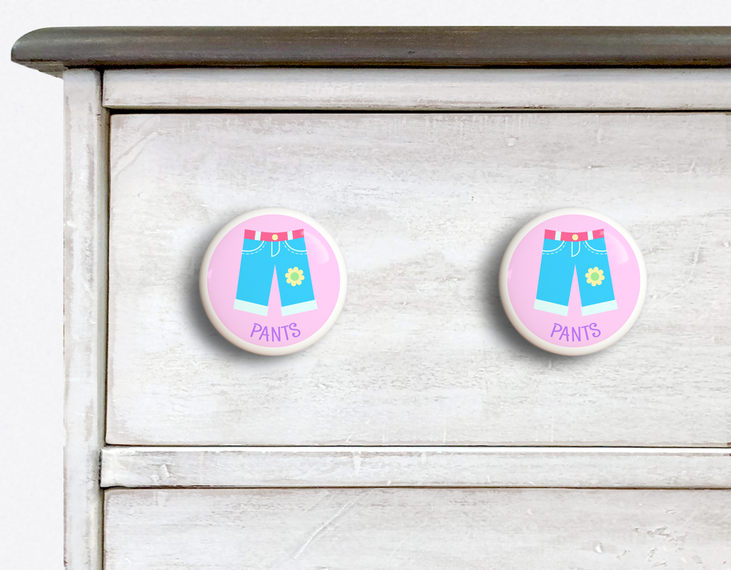 2 Ceramic drawer knobs on a dresser, girls pants on a pink ground with the word Pants written below