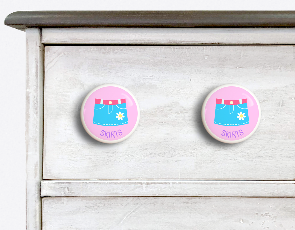 2 Ceramic drawer knobs on a dresser, Girls skirt on a pink ground with the word Skirts written below