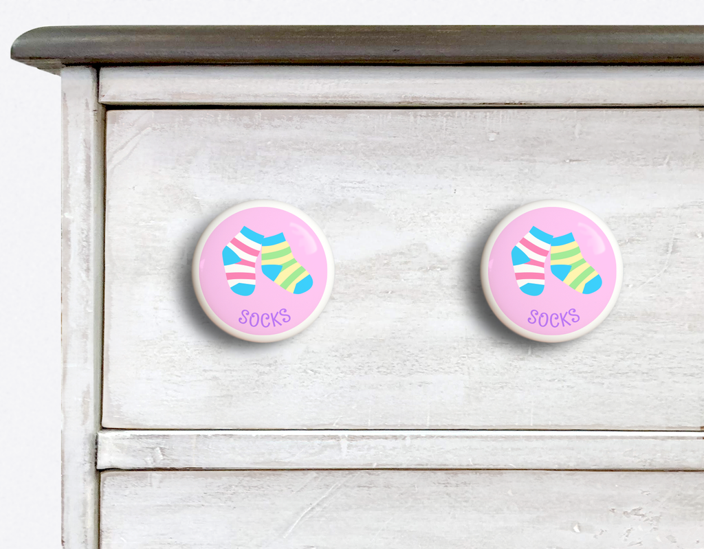 2 Ceramic drawer knobs on a dresser, striped socks on a pink ground with the word socks written below
