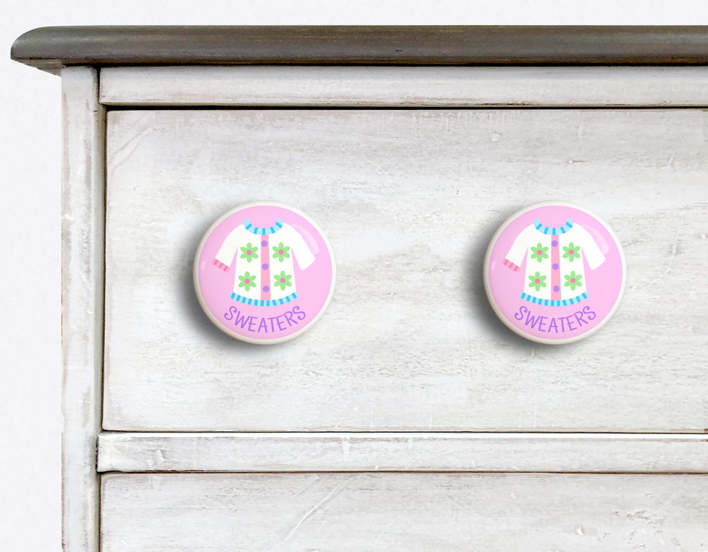 2 Ceramic drawer knobs on a dresser, girls sweater on a pink ground with the word Sweaters written below
