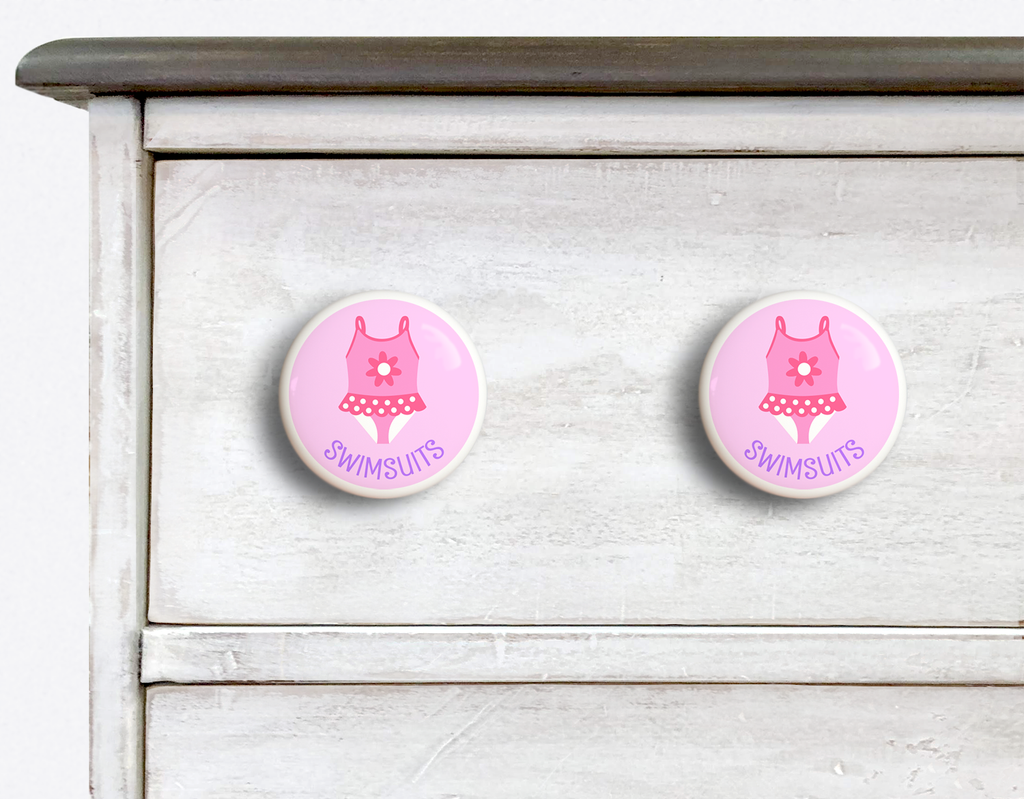 2 Ceramic drawer knobs on a dresser, Girl's bathing suit on a pink ground with the word Swimsuit written below
