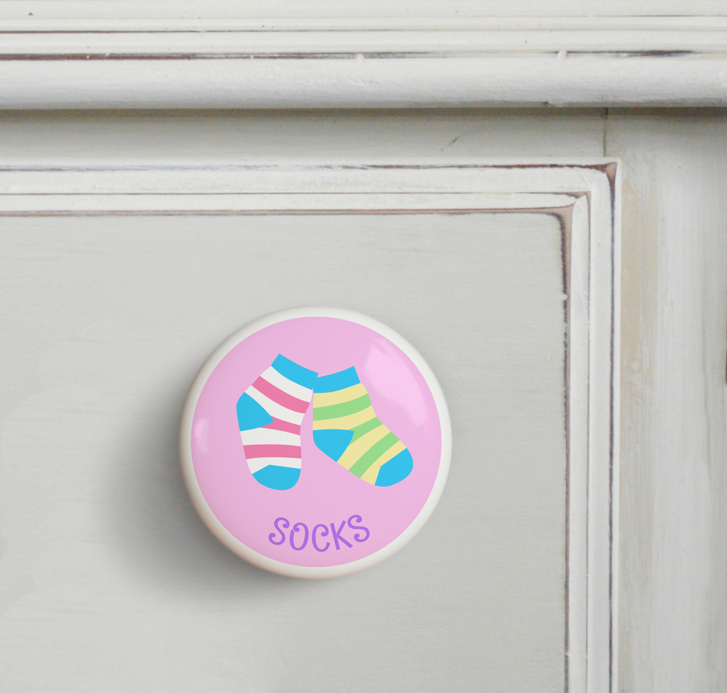 Ceramic drawer knob on a dresser, striped girls socks on a pink background with the word Socks written below