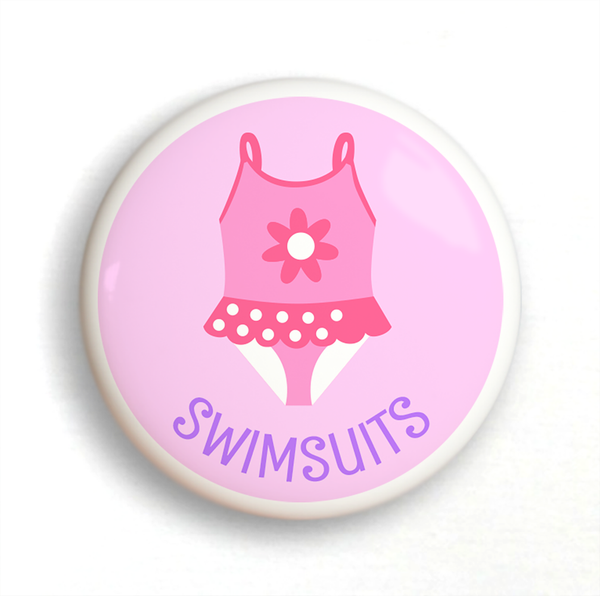Ceramic drawer knob, girl's bathing suit on a pink background with the word Swimsuits written below