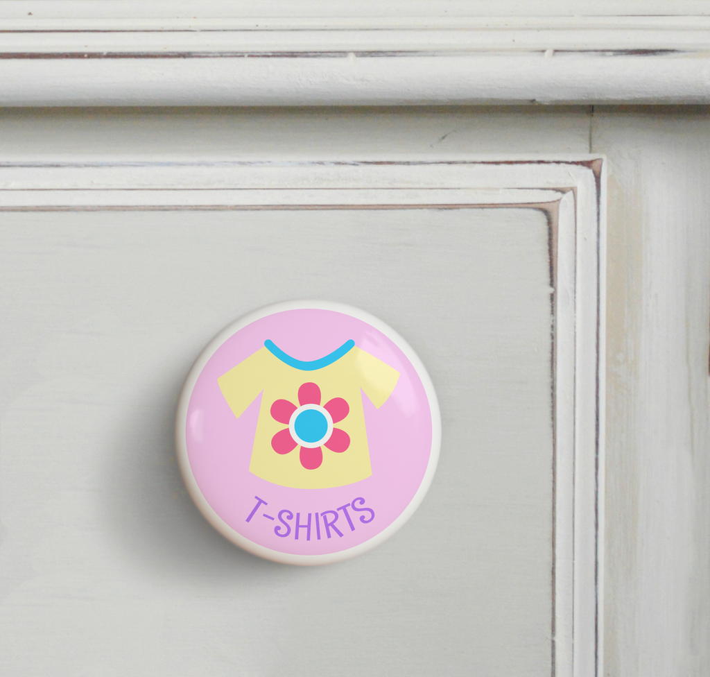 Ceramic drawer knob on a dresser, with a yellow girl's t-shirt on a pink background with the word T-Shirts written below