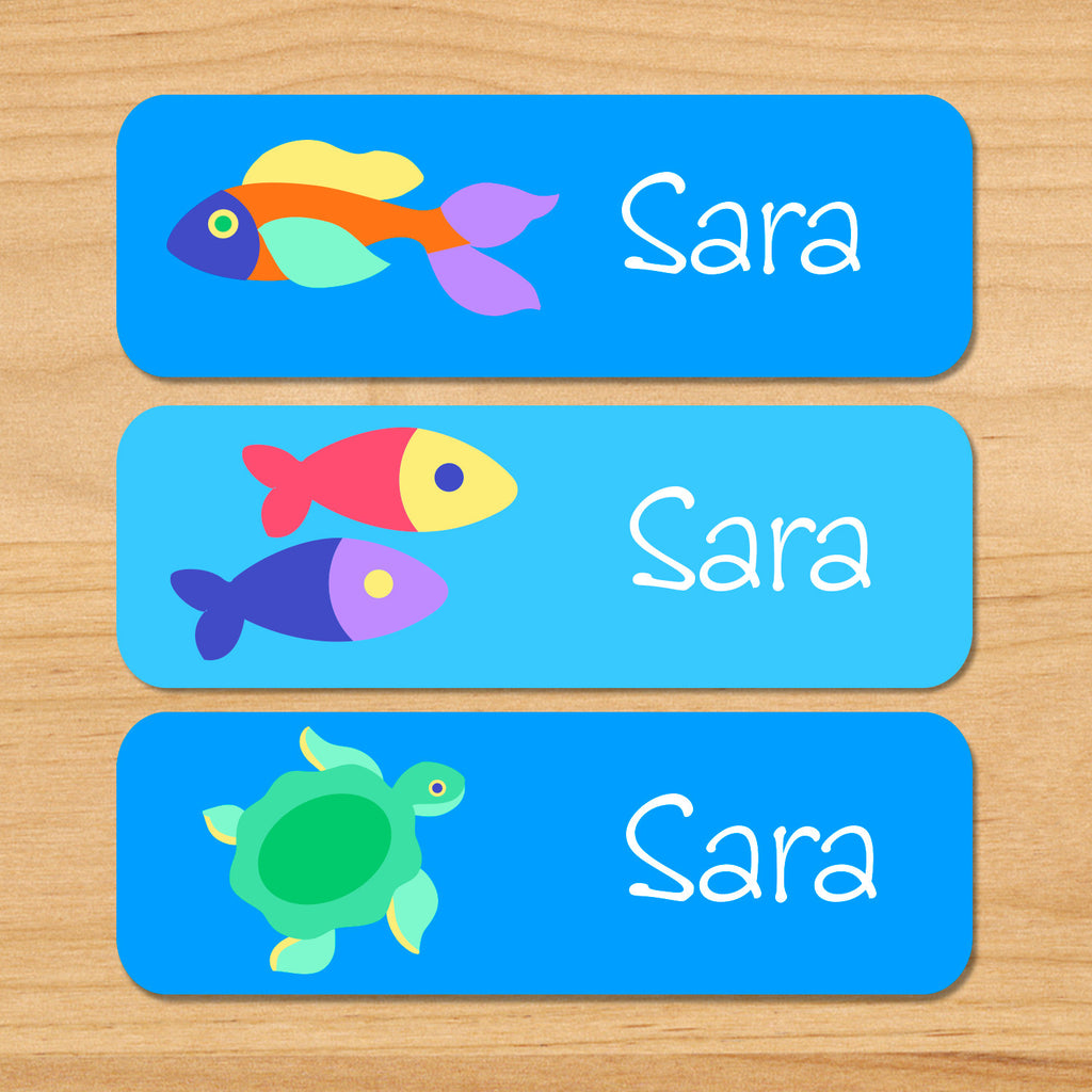 Somethin' fishy personalized ocean kids waterproof labels with name, colorful fish, and sea turtle on blue ocean water background