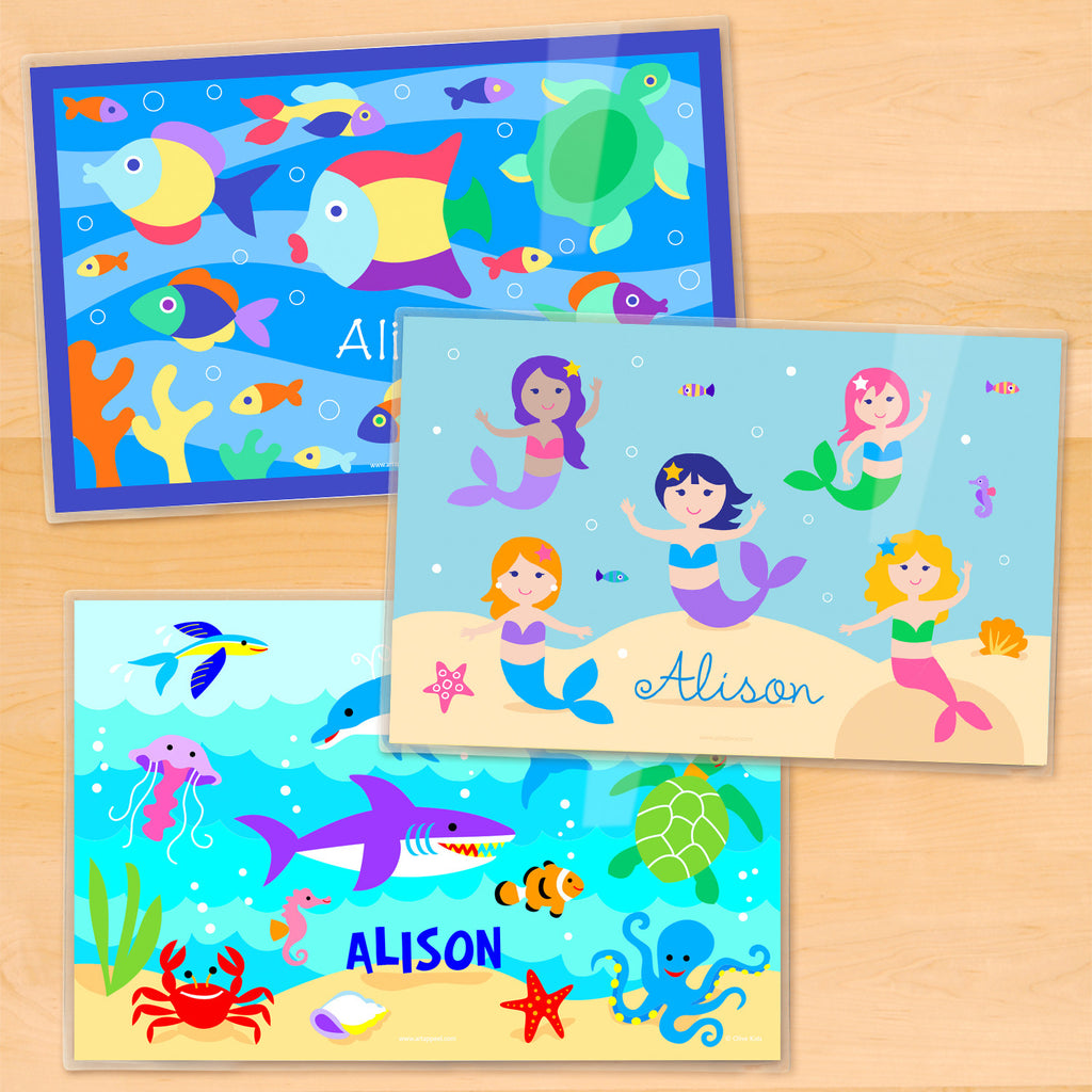 Girls personalized ocean themed placemats with colorful mermaids, playful dolphins, and tropical fish under the sea