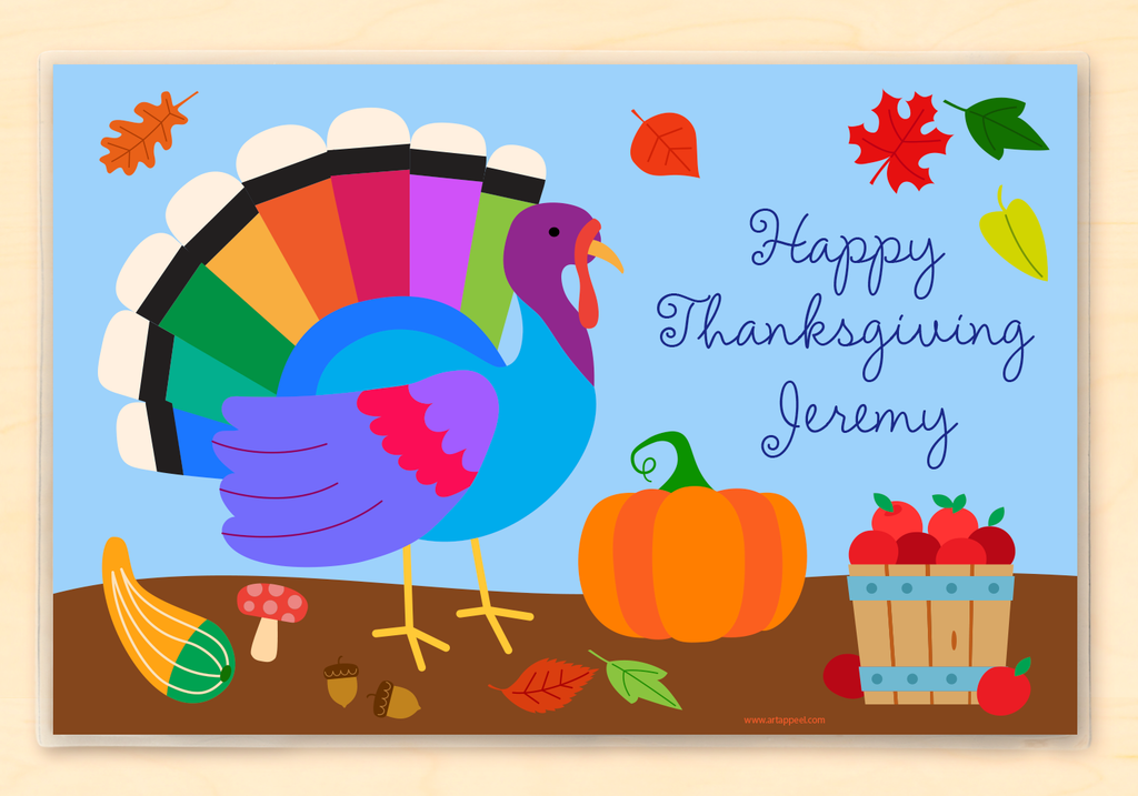 Thanksgiving placemat features a colorful turkey, pumpkin and basket of apples on a blue background. Personalized with child's name