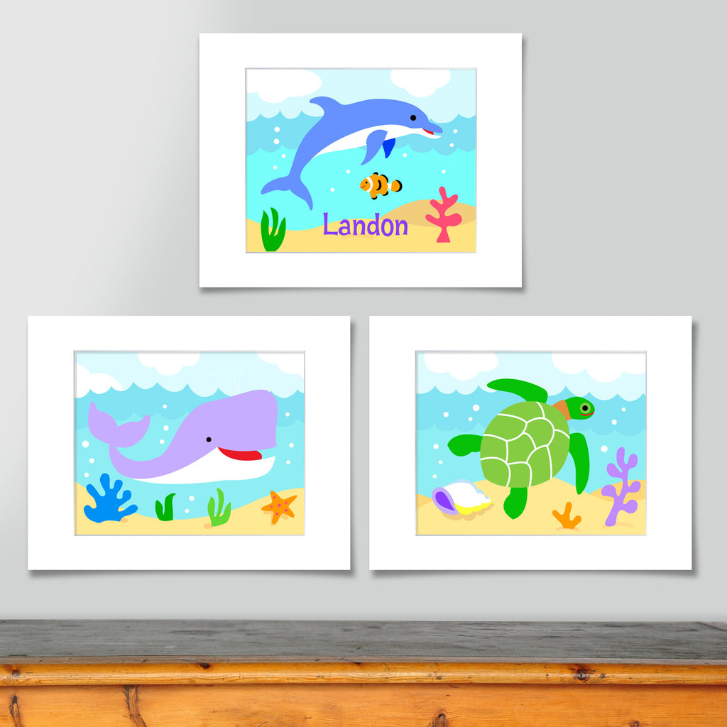 Set of 3 ocean themed prints. Blue dolphin personalized with your childs name, purple whale, and green sea turtle. Each on a sea blue scenic background.