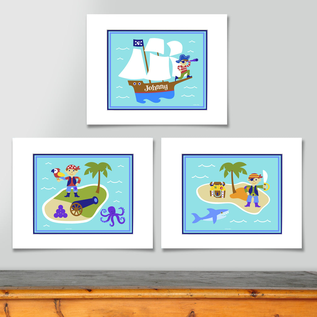 Prints include personalized pirate ship, pirate and treasue chest on an island, and pirate with a parrot on an island. All on sea blue ocean and waves background.