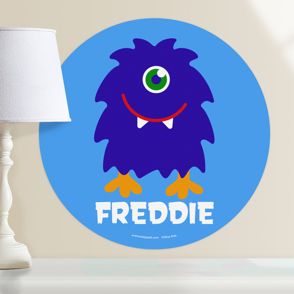 Kids monster personalized wall decal with a happy, shaggy dark blue, one eyed monster on a light blue background.  Circle shape decal.