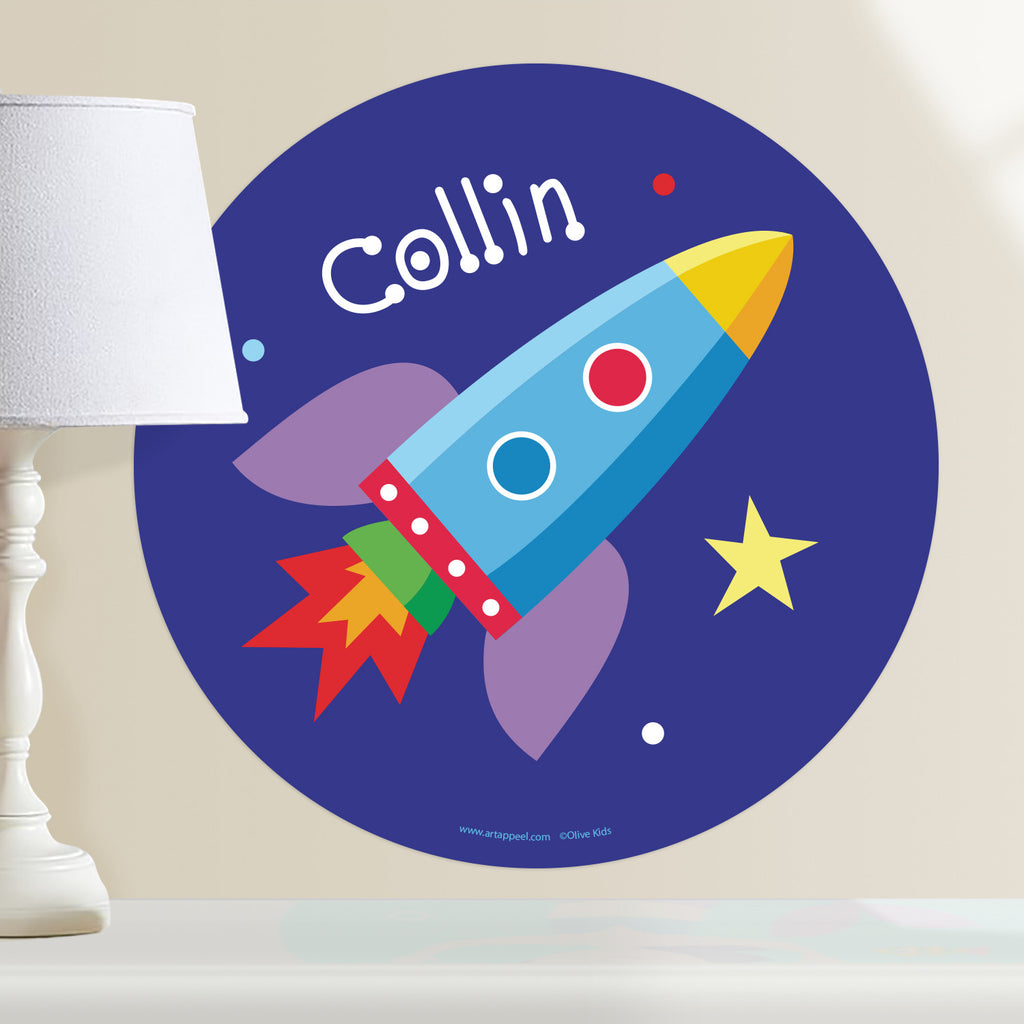 Rocket ship personalized kids wall decal.  Space theme features colorful rocketship on dark blue background with stars. Circle shape.
