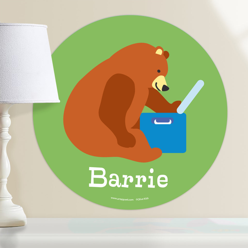 Personalized circular wall decal with a kid's name and a green background featuring a brown bear eating out of a cooler on a camping trip