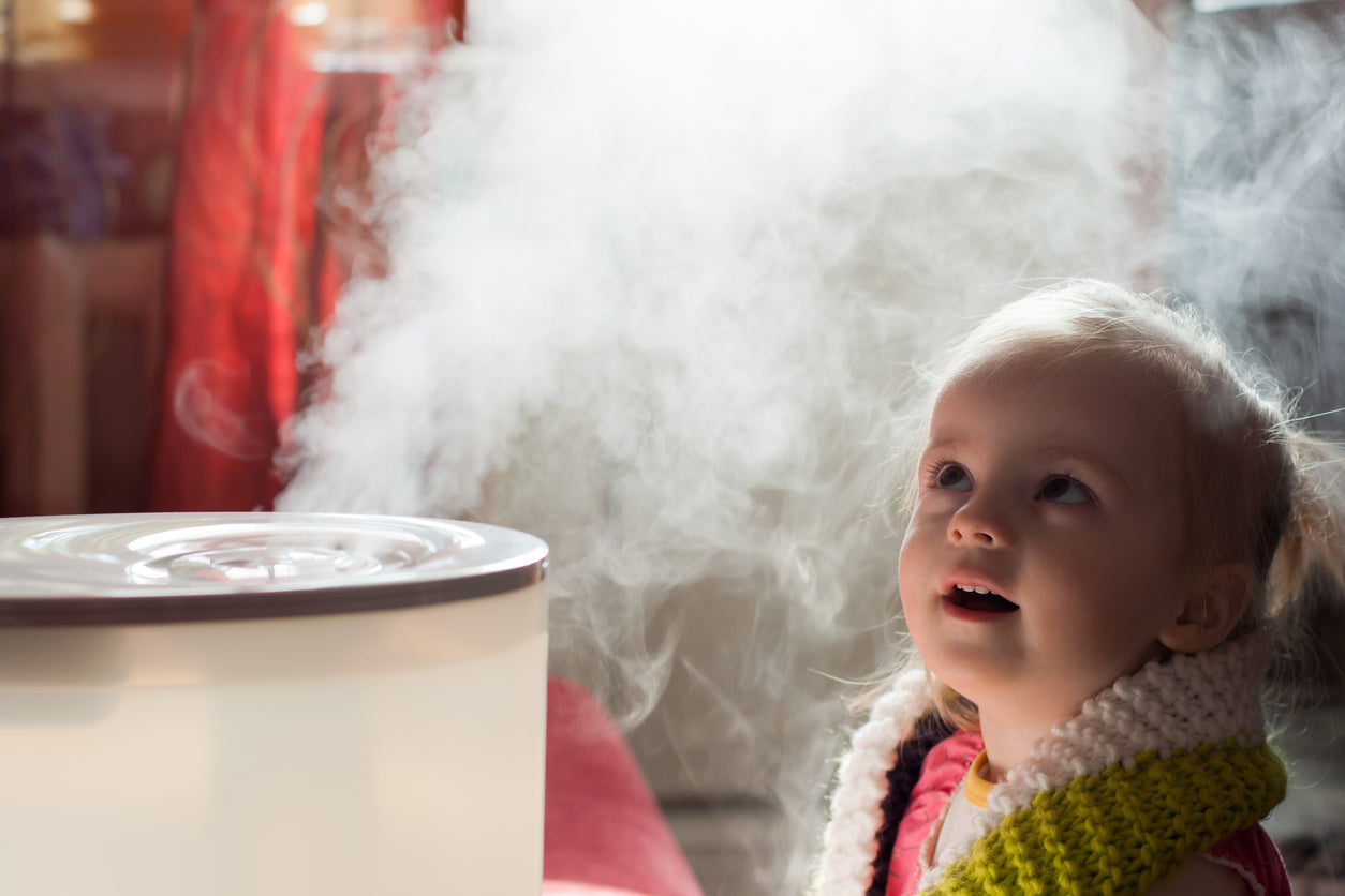 young girl watching mist from humidifier