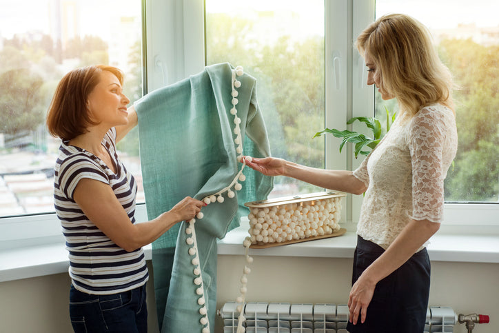 women looking at heavy drapery for home