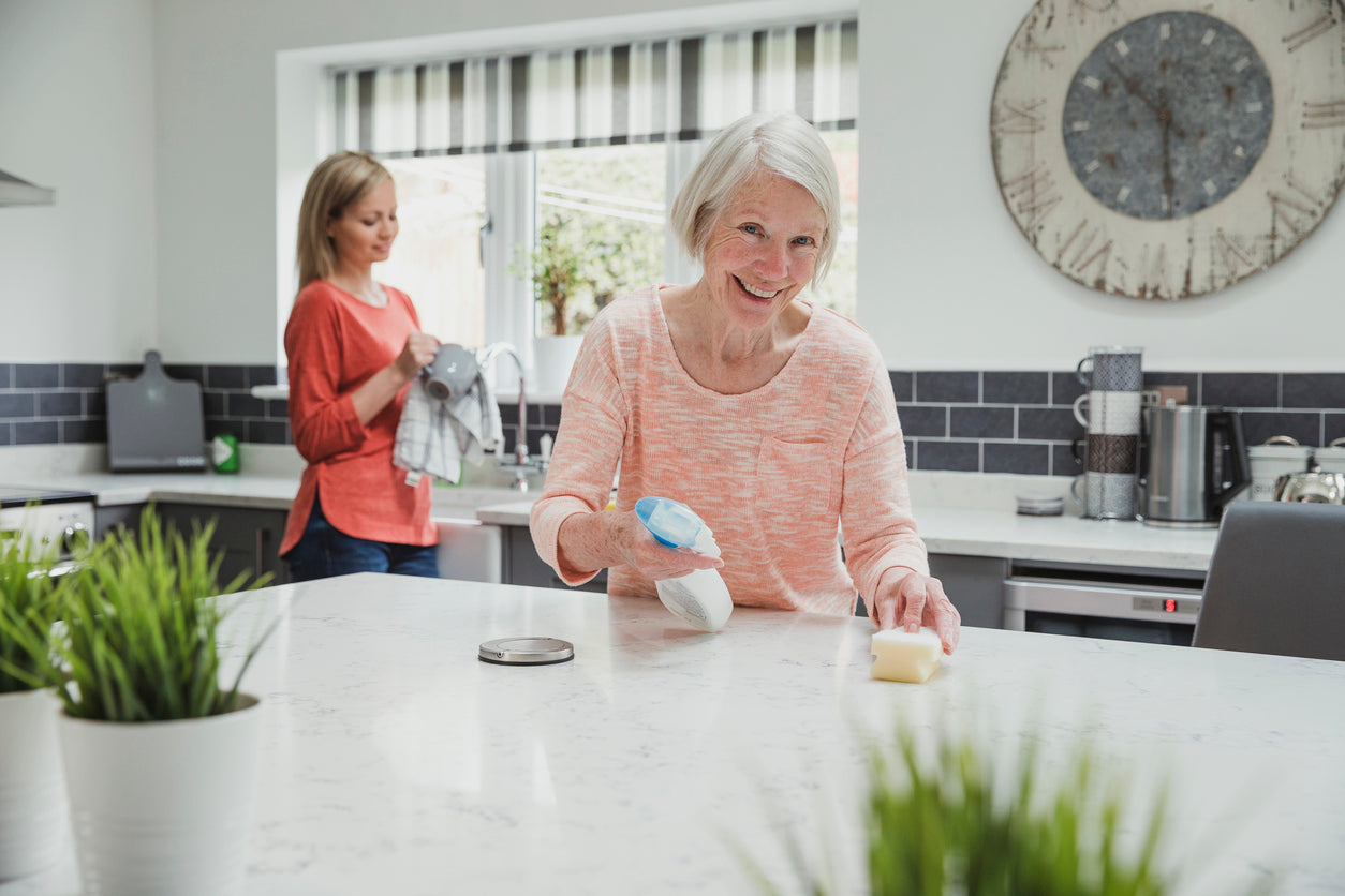 elderly mother and daughter cleaning kitchen in winter