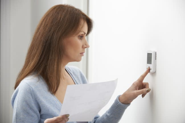 Worried Woman Turning Down Central Heating Thermostat