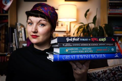 Danny Auricle founder holding books about badass women
