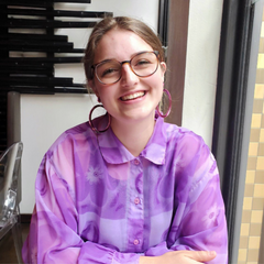 Shanae is sitting at a table in a restaurant, with her arms crossed. she's wearing a see-through light and dark purple shirt and large round purple earrings. Shanae is smiling at the camera.